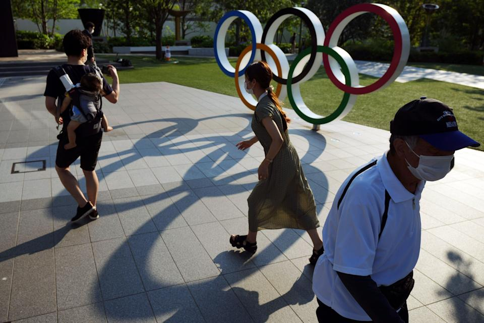 People walking past the Olympic rings in Tokyo. The Japanese public has generally been opposed to the Games, partly over fears that coronavirus levels will spike as about 100,000 people enter the country (AP)
