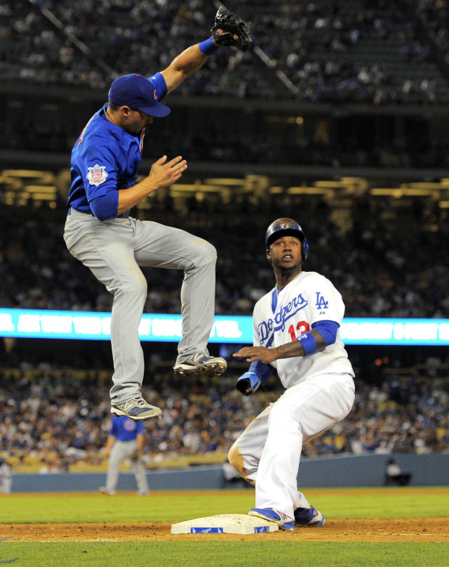 Chicago Cubs first baseman Cody Ransom, left, can't reach a high throw from starting pitcher Travis Wood as Los Angeles Dodgers' Hanley Ramirez looks on during the sixth inning of their baseball game, Tuesday, Aug. 27, 2013, in Los Angeles. Ramirez advanced to second on the play. (AP Photo/Mark J. Terrill)