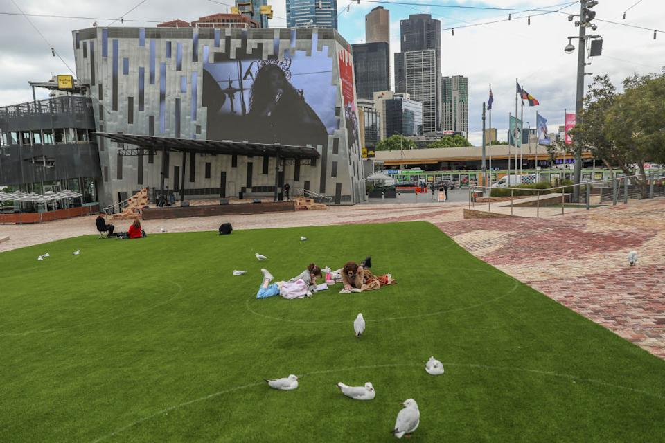Two women are seen laying down inside a marked circle setup to encourage social distancing at Federation Square in Melbourne, Australia.