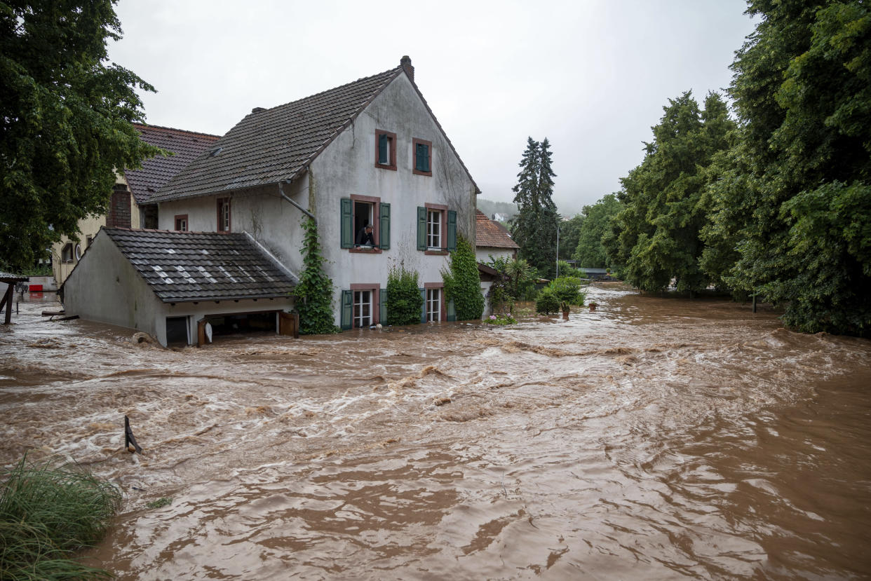 Houses are submerged on the overflowed river banks in Erdorf, Germany, as the village was flooded Thursday, July 15, 2021. Continuous rainfall has flooded numerous villages and cellars in Rhineland-Palatinate, southwestern Germany. (Harald Tittel/dpa via AP)