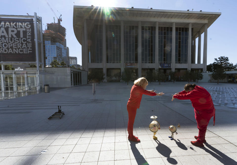 Members of the Bob Baker Marionette Theater keep their social distance as they practice on the Dorothy Chandler Pavilion's courtyard in Los Angeles Friday, Feb. 5, 2021. Due to the coronavirus pandemic, the Bob Baker Marionettes have gone digital worldwide, as the public can now tune in for a personalized Zoom puppet experience. (AP Photo/Damian Dovarganes)