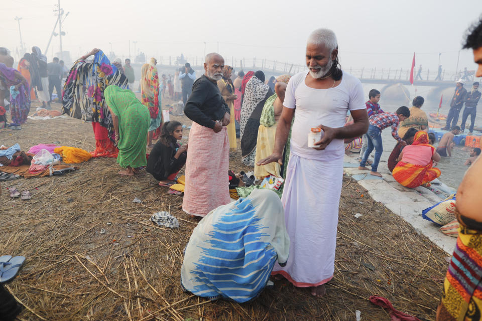 Virender Kumar Shukla, a Kalpvasi or a devotee who chooses to stay for the entire time of the festival, blesses his wife as she touches his feet after a holy dip at the Sangam during Magh mela festival, in Prayagraj, India. Friday, Feb. 19, 2021. Millions of people have joined a 45-day long Hindu bathing festival in this northern Indian city, where devotees take a holy dip at Sangam, the sacred confluence of the rivers Ganga, Yamuna and the mythical Saraswati. Here, they bathe on certain days considered to be auspicious in the belief that they be cleansed of all sins. (AP Photo/Rajesh Kumar Singh)