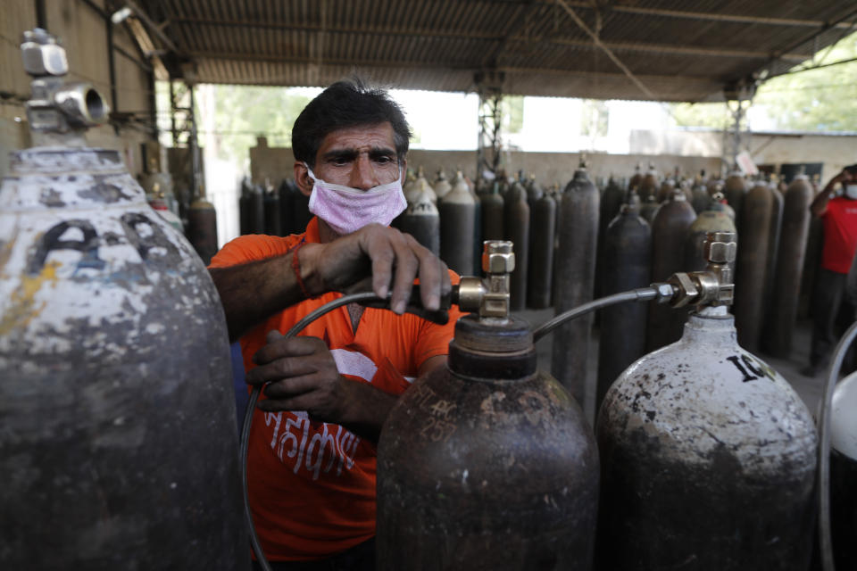 A worker refills medical oxygen cylinders at a charging station on the outskirts of Prayagraj, India, Friday, April 23, 2021. India put oxygen tankers on special express trains as major hospitals in New Delhi on Friday begged on social media for more supplies to save COVID-19 patients who are struggling to breathe. India's underfunded health system is tattering as the world's worst coronavirus surge wears out the nation, which set another global record in daily infections for a third straight day Saturday with 346,786. (AP Photo/Rajesh Kumar Singh)