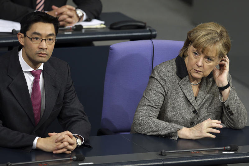 German Chancellor Angela Merkel, right, and German Economy Minister and Vice-Chancellor and minister of  economic affaires,  Philipp Roesler, left, attend a meeting of the German federal parliament, Bundestag, in Berlin, Germany, Wednesday, Jan. 16, 2013. (AP Photo/Michael Sohn)