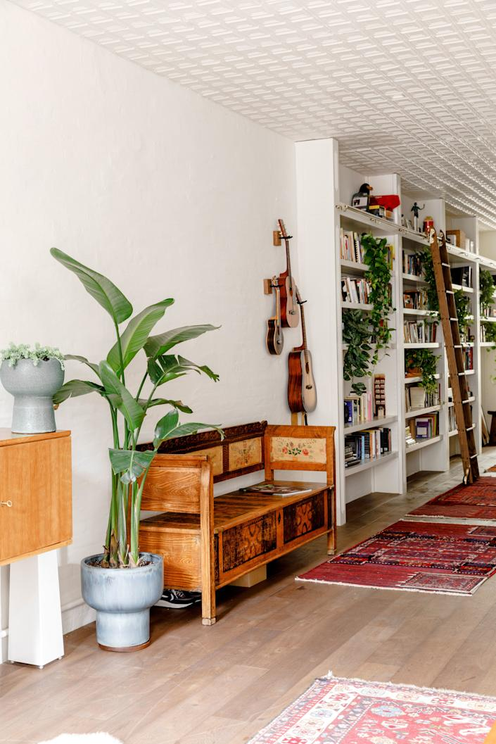 The hallway boasts custom-designed bookcases from Gramercy Design that were constructed by Stephen Fanuka. The ladder has a dual purpose: Besides offering access to books, it can be removed and hooked onto rails in the kitchen to reach high cabinets. The tin ceiling is originally from a factory in Pennsylvania—O'Donnell sourced it from Demolition Depot and had the panels stripped and refinished in white.