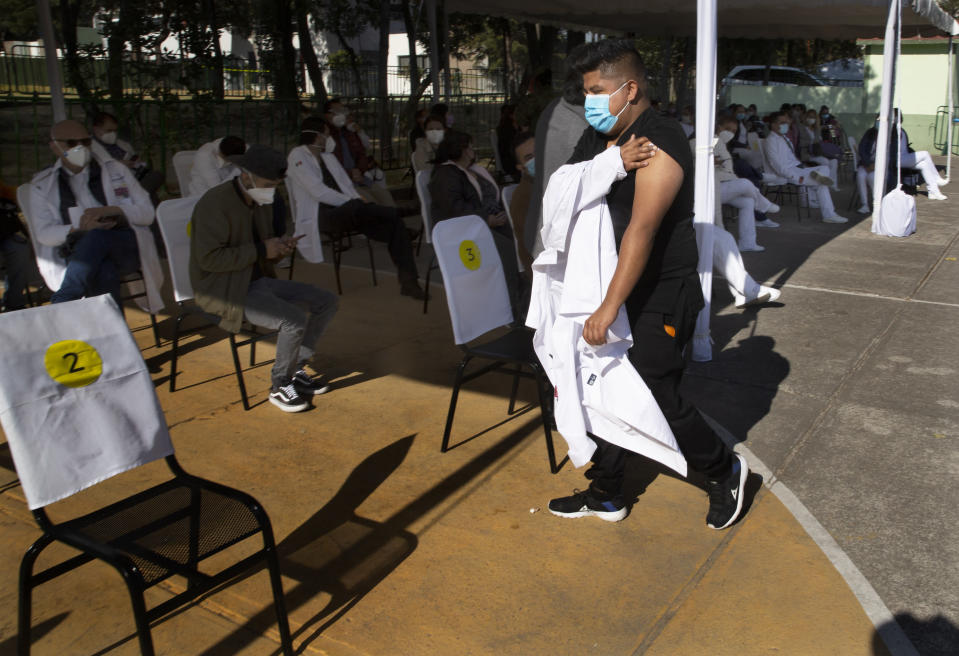 A health worker holds his arm where he was given a shot of the Pfizer-BioNTech vaccine for COVID-19 as he arrives to sit in an observation area at the N-1 military base in Mexico City, Wednesday, Dec. 30, 2020. (AP Photo/Marco Ugarte)