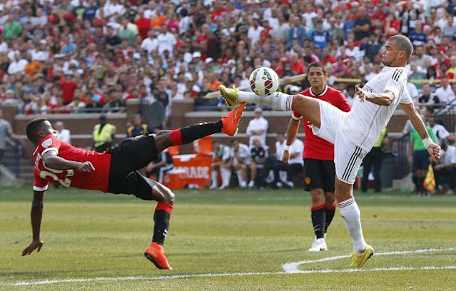 Manchester United forward Wilfried Zaha, left, and Real Madrid defender Pepe battle for the ball during a Guinness International Champions Cup soccer match at Michigan Stadium in Ann Arbor, Mich., Saturday, Aug. 2, 2014. Manchester United won 3-1. (AP Photo/Paul Sancya)