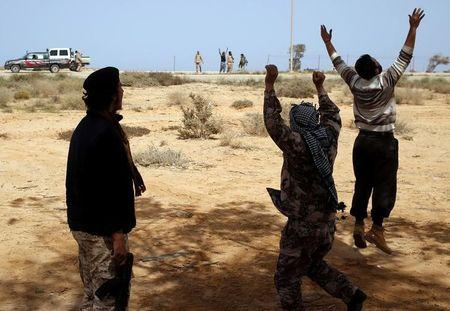 Libya Dawn fighters celebrate as a Libya Dawn aircraft bombed Islamic State militant positions near Sirte