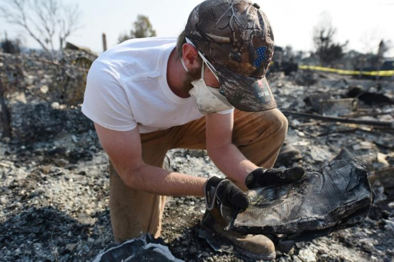 Ben Pederson looks at a burnt school yearbook after his family's home was destroyed by wildfire in Santa Rosa, California