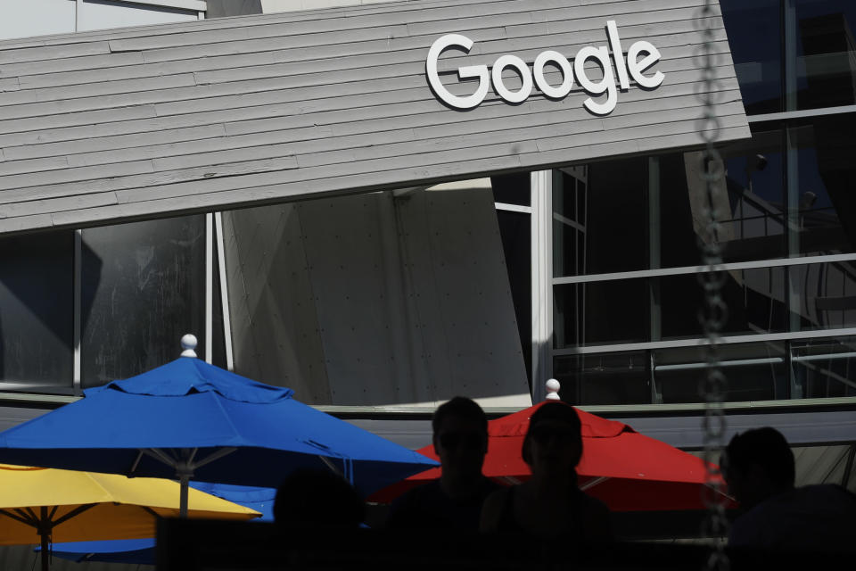 FILE - In this Sept. 24, 2019, file photo people walk by a Google sign on the campus in Mountain View, Calif. Alphabet's board of directors is investigating claims of sexual misconduct made against executives and how the company handled the allegations. (AP Photo/Jeff Chiu, File)