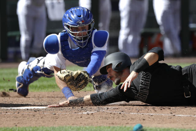 Seattle Mariners' Austin Nola, right, touches the plate ahead of the tag by Toronto Blue Jays catcher Reese McGuire to score in the seventh inning of a baseball game Sunday, Aug. 25, 2019, in Seattle. (AP Photo/Elaine Thompson)