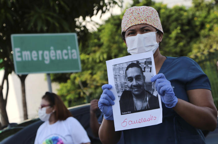 """A health worker holds a photo of a person he said was his colleague who died of COVID-19, at a protest outside """"Pronto Socorro 28 de Agosto"""" Hospital in Manaus, Brazil, Monday, April 27, 2020. Cases of the new coronavirus are overwhelming hospitals, morgues and cemeteries across Brazil as Latin America's largest nation veers closer to becoming one of the world's pandemic hot spots. (AP Photo/Edmar Barros)"""