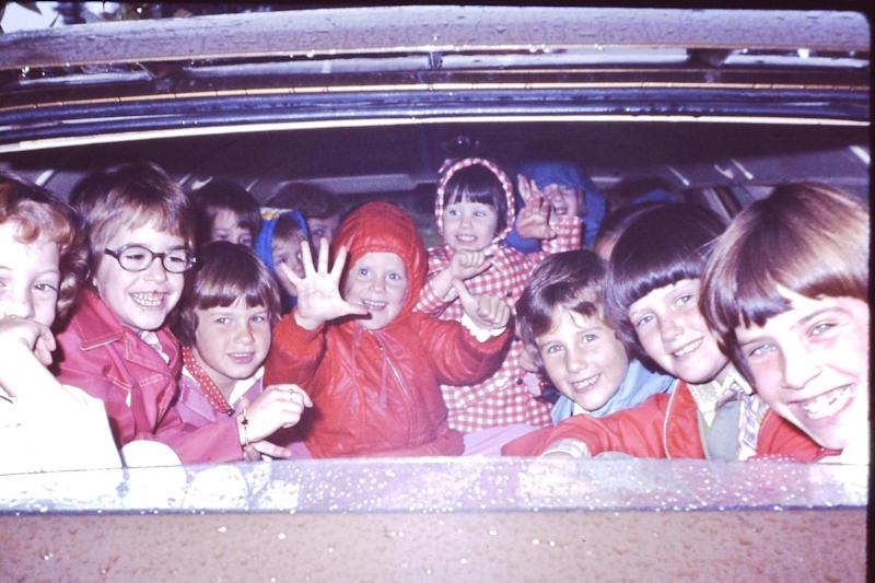 Heidi sits center, in the red hooded coat. Her little sister is next to her, wearing the gingham coat. Her older sister is second from the far right.