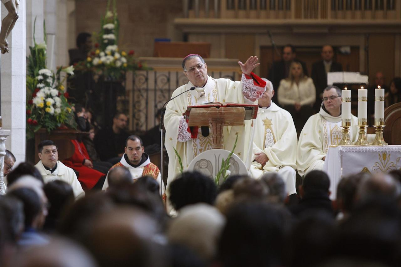 Latin Patriarch of Jerusalem Fouad Twal, center, leads a Christmas day Mass at the Church of the Nativity, traditionally believed to be the birthplace of Jesus Christ, in the West Bank town of Bethlehem, Sunday, Dec. 25, 2011. (AP Photo/Majdi Mohammed)