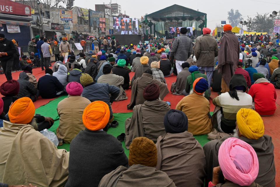 Protesting farmers listen to their leaders as they continue to demonstrate against the central government's recent agricultural reforms while blocking a highway at the Delhi-Haryana state border in Singhu on December 30, 2020. (Photo by PRAKASH SINGH/AFP via Getty Images)