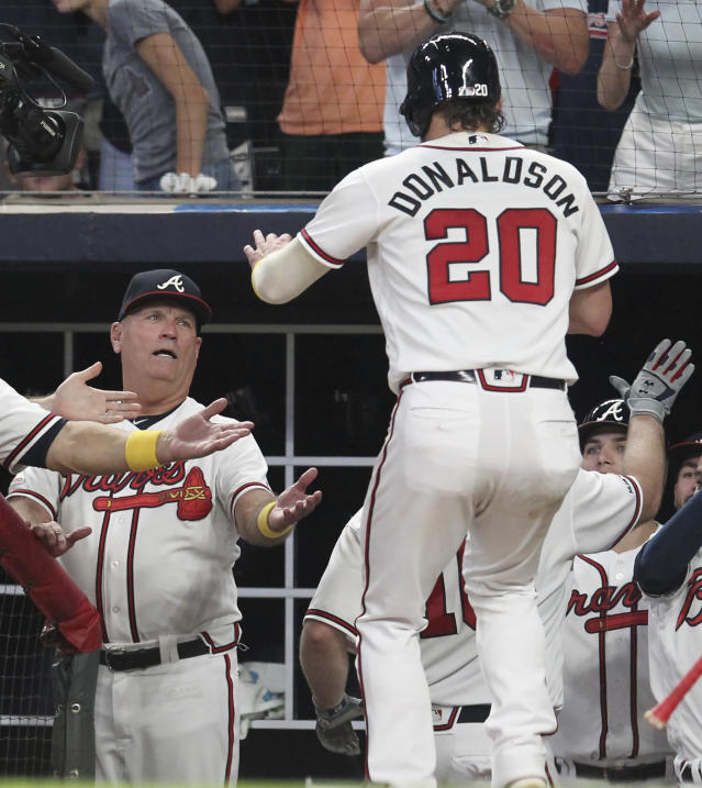 Atlanta Braves manager Brian Snitker, left, congratulates Josh Donaldson (20) who scored on a two-run home run by Brian McCann against the Washington Nationals during the sixth inning of a baseball game Saturday, Sept. 7, 2019, in Atlanta. (AP Photo/Tami Chappell)