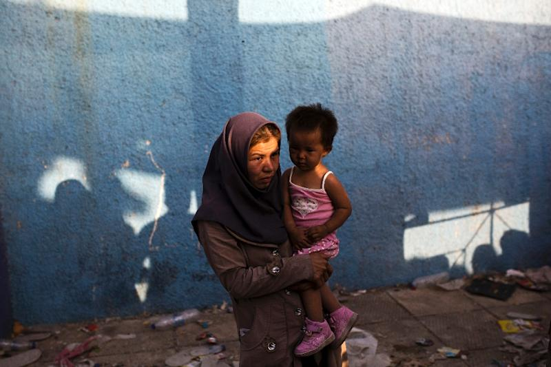 A migrant woman carries her child as she waits to be registered by the police at the Lesbos Port on September 6, 2015