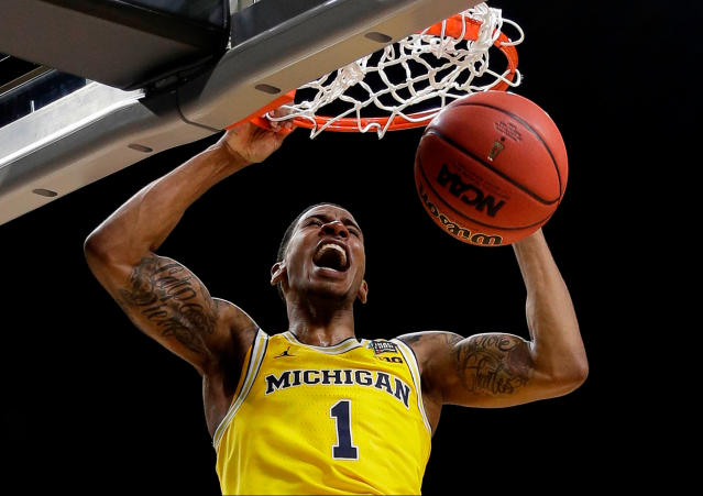 FILE - In this March 31, 2018, file photo, Michigan's Charles Matthews (1) dunks during the second half in the semifinals of the Final Four NCAA college basketball tournament against Loyola-Chicago, in San Antonio. Michigan standout Charles Matthews is entering the NBA draft without hiring an agent, giving him the option to stay in school. Matthews announced his decision on Friday, April 20, 2018. (AP Photo/David J. Phillip, File)