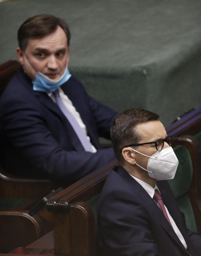 Poland's Prime Minister Mateusz Morawiecki, right, and his main opponent inside the ruling right-wing coalition, Justice Minister Zbigniew Ziobro, left, during a crucial vote in parliament in Warsaw, Poland, Tuesday, May 4, 2021. Polish lawmakers have voted to approve the nation's spending plan for the 58 billion euros ($70 billion) it expects to receive from the European Union's pandemic recovery plan. (AP Photo/Czarek Sokolowski)