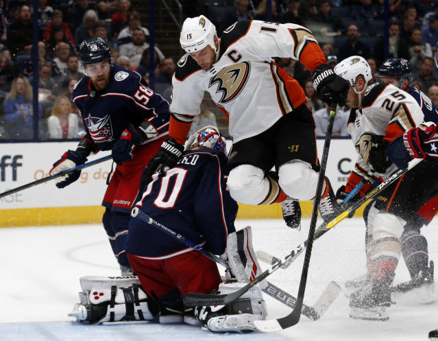 Anaheim Ducks forward Ryan Getzlaf (15) jumps next to Columbus Blue Jackets goalie Joonas Korpisalo (70), of Finland, as Blue Jackets defenseman David Savard (58) and Ducks forward Ondrej Kase (25), of the Czech Republic, watch during the first period of an NHL hockey game in Columbus, Ohio, Friday, Oct. 11, 2019. (AP Photo/Paul Vernon)