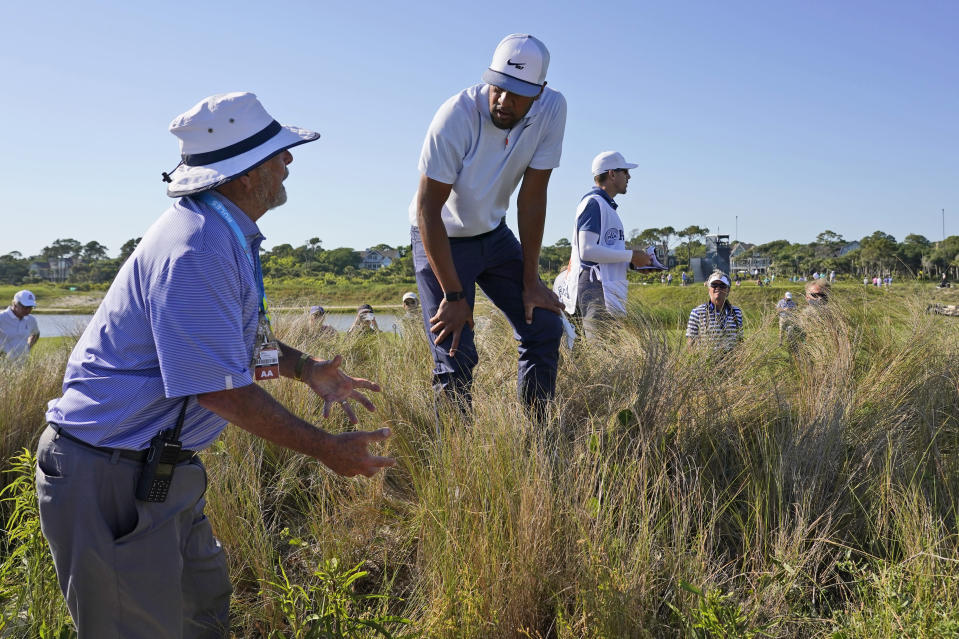 Tony Finau, right, Gets a ruling on the 16th hole during the first round of the PGA Championship golf tournament on the Ocean Course Thursday, May 20, 2021, in Kiawah Island, S.C. (AP Photo/Chris Carlson)