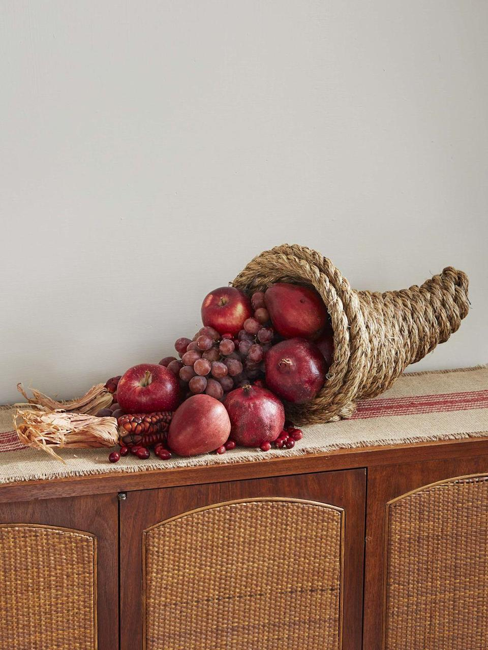 """<p>Fashion a DIY cornucopia out of just 2 materials, rope and hot glue. For a striking display fill with monochromatic bounty such as red grapes and apples, and pomegranates. <strong><br></strong></p><p><strong>To make:</strong> Fold the end of a long length of 3/4-inch manila or jute rope over on itself about 4 inches. Start wrapping the long length of rope around the folded piece, forming the cornucopia, arching it and making it wider as you work, holding everything together with hot glue. When you get to the desired size, do one last pass between and on top of the last two rows then add a circle of rope on the bottom to act as a base and keep it from rolling.</p><p><a class=""""link rapid-noclick-resp"""" href=""""https://www.amazon.com/Twisted-Manila-Rope-Hemp-Landscaping/dp/B01J07102A/ref=sr_1_13?linkCode=ogi&tag=syn-yahoo-20&ascsubtag=%5Bartid%7C10050.g.2063%5Bsrc%7Cyahoo-us"""" rel=""""nofollow noopener"""" target=""""_blank"""" data-ylk=""""slk:SHOP ROPE"""">SHOP ROPE</a></p>"""