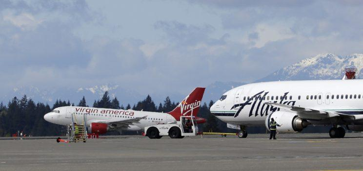 A Virgin America plane takes off past an Alaska Airlines plane at Seattle-Tacoma International Airport in Seattle. (AP)