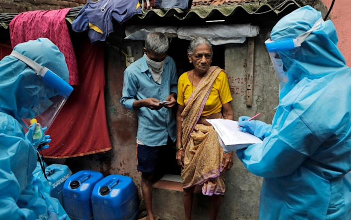 Health workers screen residents for Covid-19 symptoms at Devnar slum in Mumbai, India, as the country surpasses 800,000 cases - AP