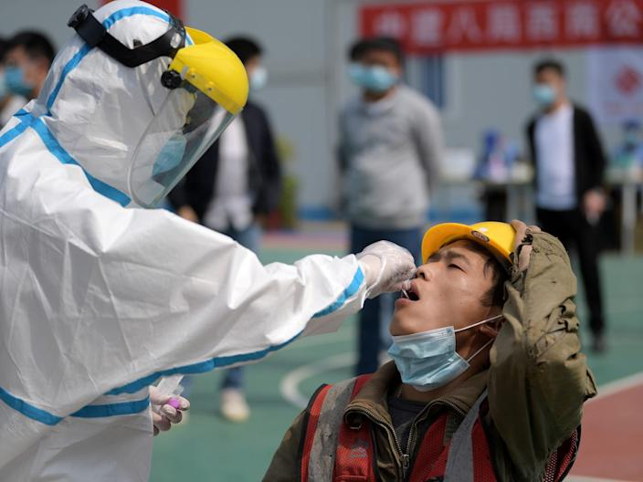 A worker collects a swab from a construction worker for nucleic acid test in Wuhan in China on April 7, 2020.