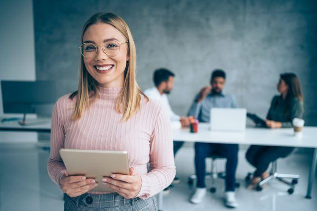 Shot of a beautiful smiling businesswoman standing in front of her team and holding digital tablet. Portrait of successful businesswoman standing with her colleagues working in background. Multi-ethnic group of creative people on a business meeting in board room. (Photo: VioletaStoimenova via Getty Images)
