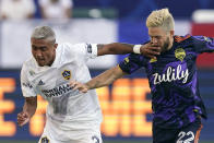 LA Galaxy defender Julian Araujo, left, hits Seattle Sounders midfielder Kelyn Rowe in the face as they battle for the ball during the first half of a Major League Soccer match Saturday, June 19, 2021, in Carson, Calif. (AP Photo/Mark J. Terrill)