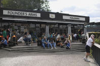 People sit outside a pub on the south bank of river Thames in London, Monday, Aug. 31, 2020. Today is the last day of the 'Eat out to help out' scheme, the UK Government's initiative to support restaurants, cafés, bars and pubs. (AP Photo/Alberto Pezzali)