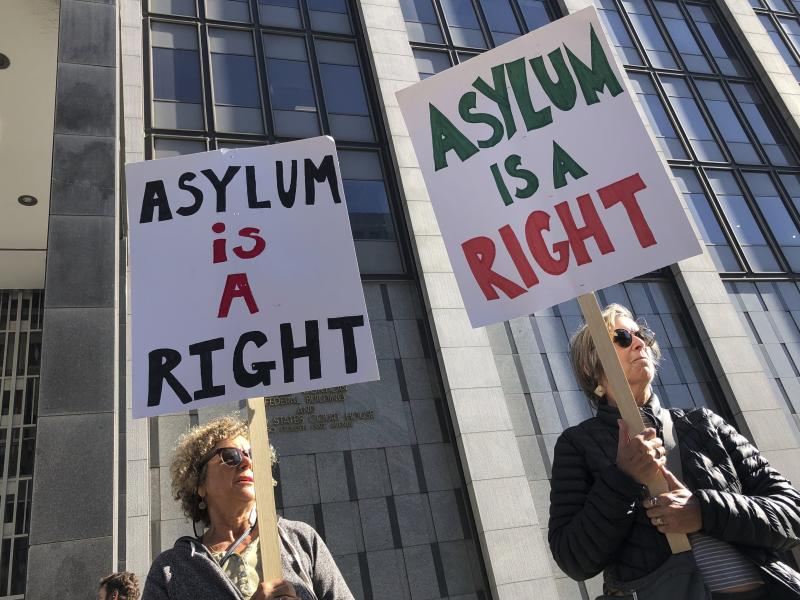 """Protestors hold signs that read """" Asylum is a Right"""" outside of the San Francisco Federal Courthouse on Wednesday, July 24, 2019 in San Francisco, Calif. A federal judge said Wednesday that the Trump administration can enforce its new restrictions on asylum for people crossing the U.S.-Mexico border while lawsuits challenging the policy play out.  (AP Photo/Haven Daley)"""