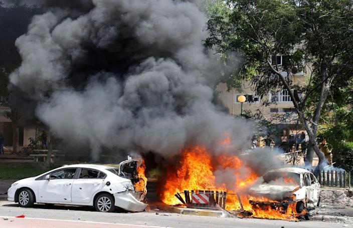 Two white cars are engulfed in flames