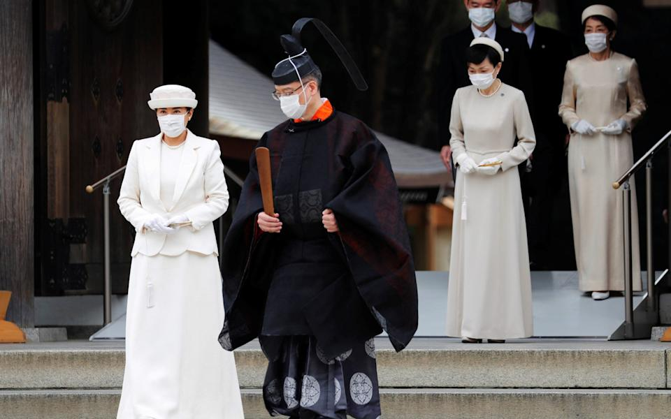 Japan's Empress Masako wears a face mask as she attends a ceremony during a celebration marking 100 years since the enshrinement of Emperor Meiji at Meiji Shrine in Tokyo - Reuters