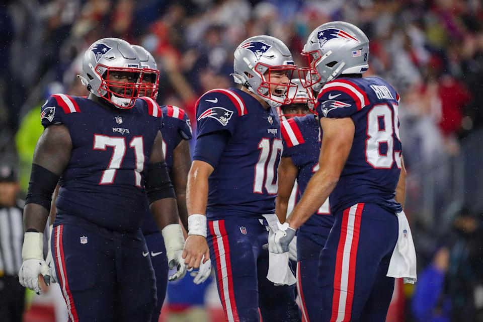 New England Patriots offensive guard Mike Onwenu (71) and quarterback Mac Jones (10) and tight end Hunter Henry (85) celebrate a touchdown against the Tampa Bay Buccaneers during the second quarter at Gillette Stadium in Foxboro on Sunday, Oct. 3, 2021.