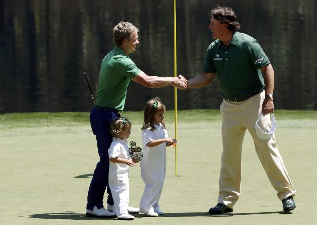 Golfers Luke Donald (L) of Britain and Phil Mickelson of the United States shake hands on the ninth green during the Par 3 Contest ahead of the 2014 Masters golf tournament at the Augusta National Golf Club in Augusta, Georgia April 9, 2014. Below the golfers are Donald's two daughters Sophia (2nd L) and Ellie (C). REUTERS/Jim Young (UNITED STATES - Tags: SPORT GOLF)
