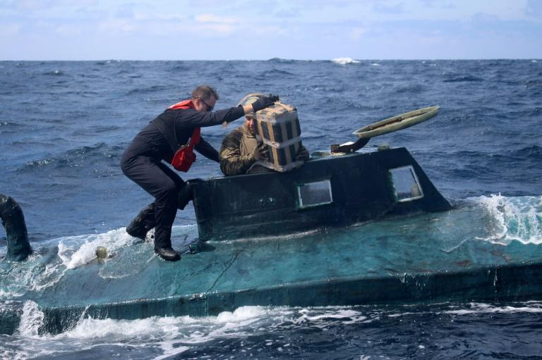 A US Coast Guard boarding team extracts drugs from a smuggling vessel off the coast of South America on September 1, 2019