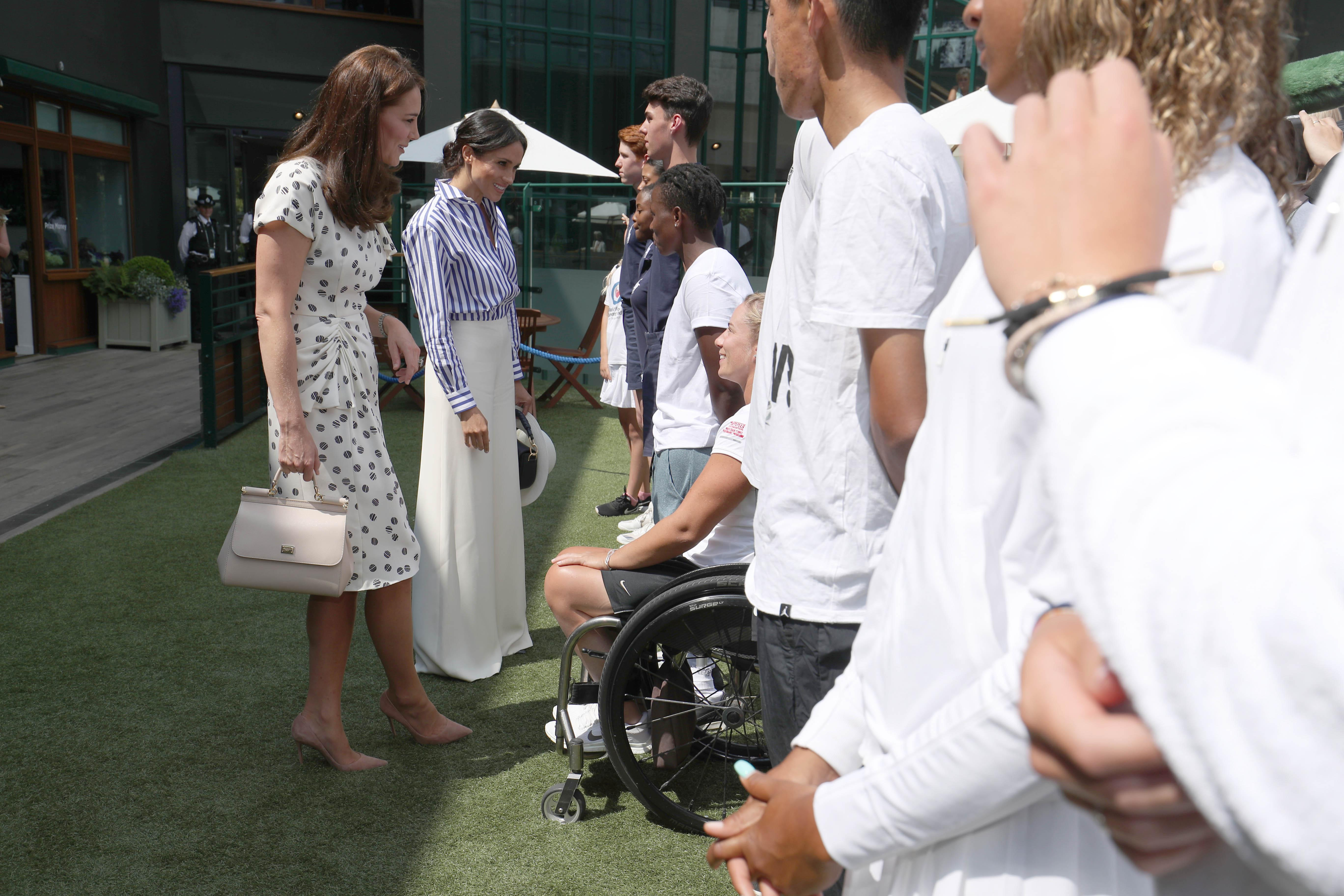 LONDON, ENGLAND - JULY 14: Catherine, Duchess of Cambridge and Meghan, Duchess of Sussex meet Wheelchair competitors Lucy Shuker of Great Britain and KG Montjane of South Africa during a visit to the Wimbledon Championships at All England Lawn Tennis and Croquet Club on July 14, 2018 in London, England. (Photo by Jonathan Brady - WPA Pool/Getty Images)