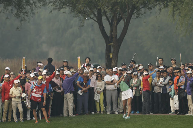 Spectators watch Jessica Korda of the United States driving a ball on the 18th hole during the second round of the Reignwood LPGA Classic golf tournament at Pine Valley Golf Club on the outskirts of Beijing, China, Friday, Oct. 4, 2013. (AP Photo/Alexander F. Yuan)