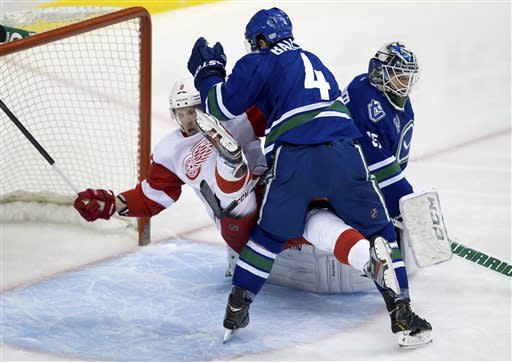 Vancouver Canucks' Keith Ballard, center, checks Detroit Red Wings' Justin Abdelkader, left, into goalie Cory Schneider during the second period of an NHL hockey game in Vancouver, British Columbia, on Saturday, April 20, 2013. (AP Photo/The Canadian Press, Darryl Dyck)