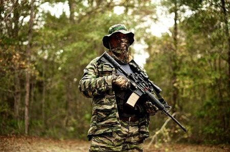 A member of the North Florida Survival Group holds an AR-15 rifle as he joins other members in performing an enemy contact drill during a field training exercise in Old Town