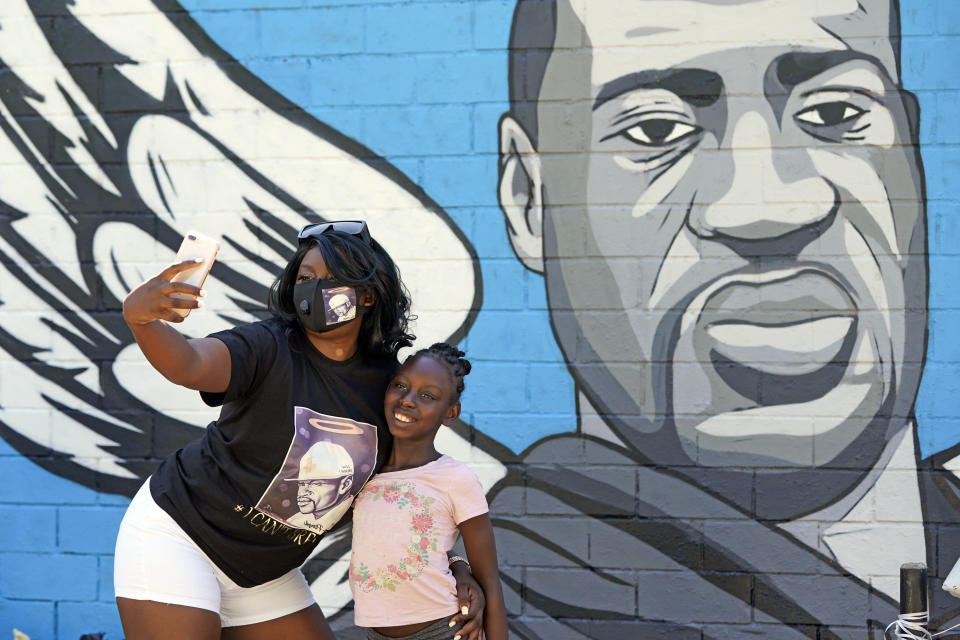 In this June 7, 2020, photo, Margaret Williams, left, takes a picture with her daughter, Nala, 8, in front of a mural honoring George Floyd in Houston's Third Ward. Floyd, who grew up in the Third Ward, died after being restrained by Minneapolis police officers on Memorial Day. (AP Photo/David J. Phillip)