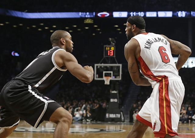 Brooklyn Nets' Alan Anderson, left, defends against Miami Heat's LeBron James, right, during the first half of an NBA basketball game on Friday, Jan. 10, 2014, in New York. Both teams wore nicknames on their jerseys during the game. (AP Photo/Frank Franklin II)