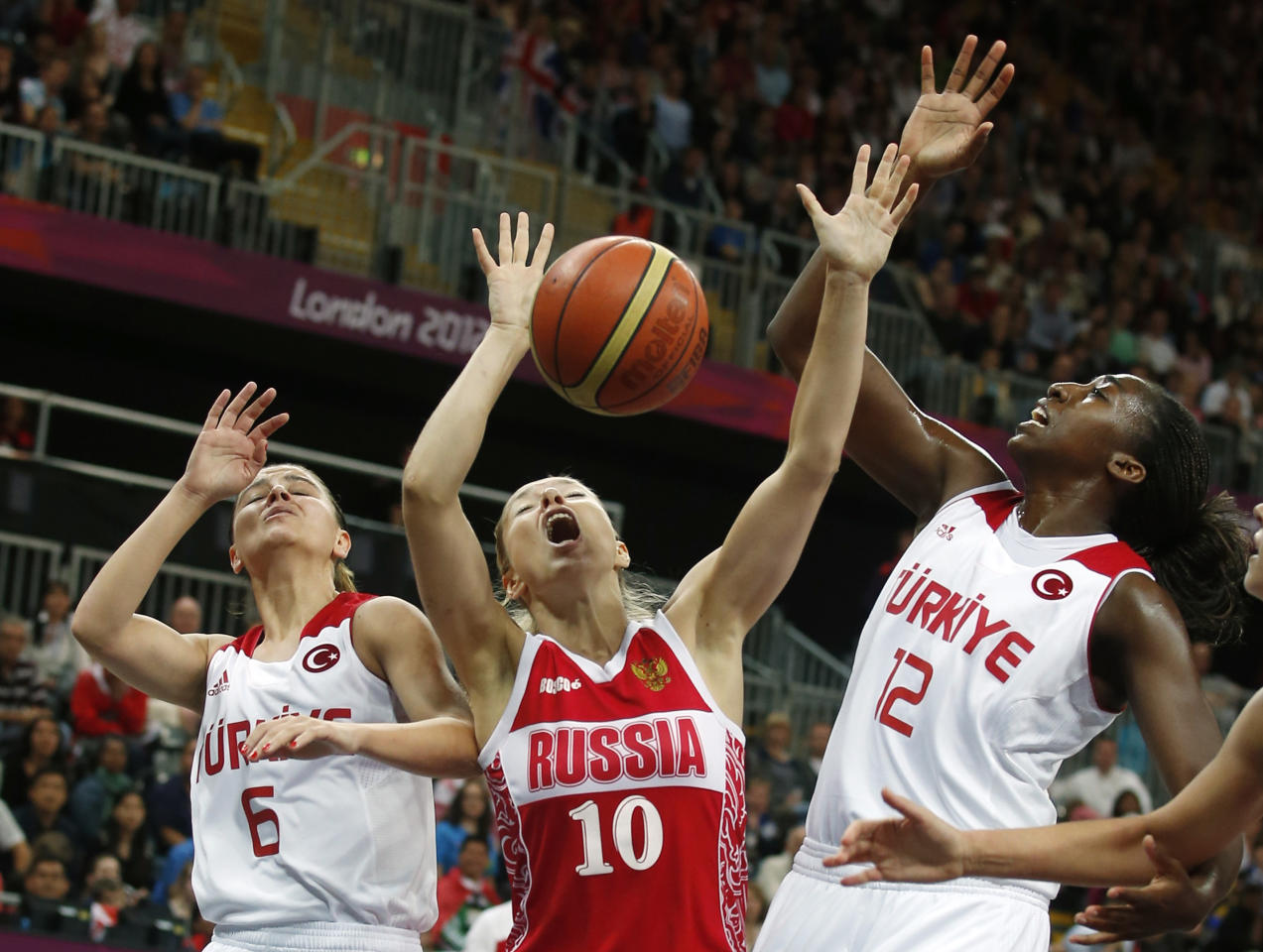Russia's Ilona Korstin (10) is guarded by Turkey's Birsel Vardarli (6) and Kuanitra Hollingsvorth (12) during the women's quarterfinal basketball match at the Basketball Arena in London during the London 2012 Olympic Games August 7, 2012. REUTERS/Sergio Perez (BRITAIN  - Tags: SPORT OLYMPICS SPORT BASKETBALL)