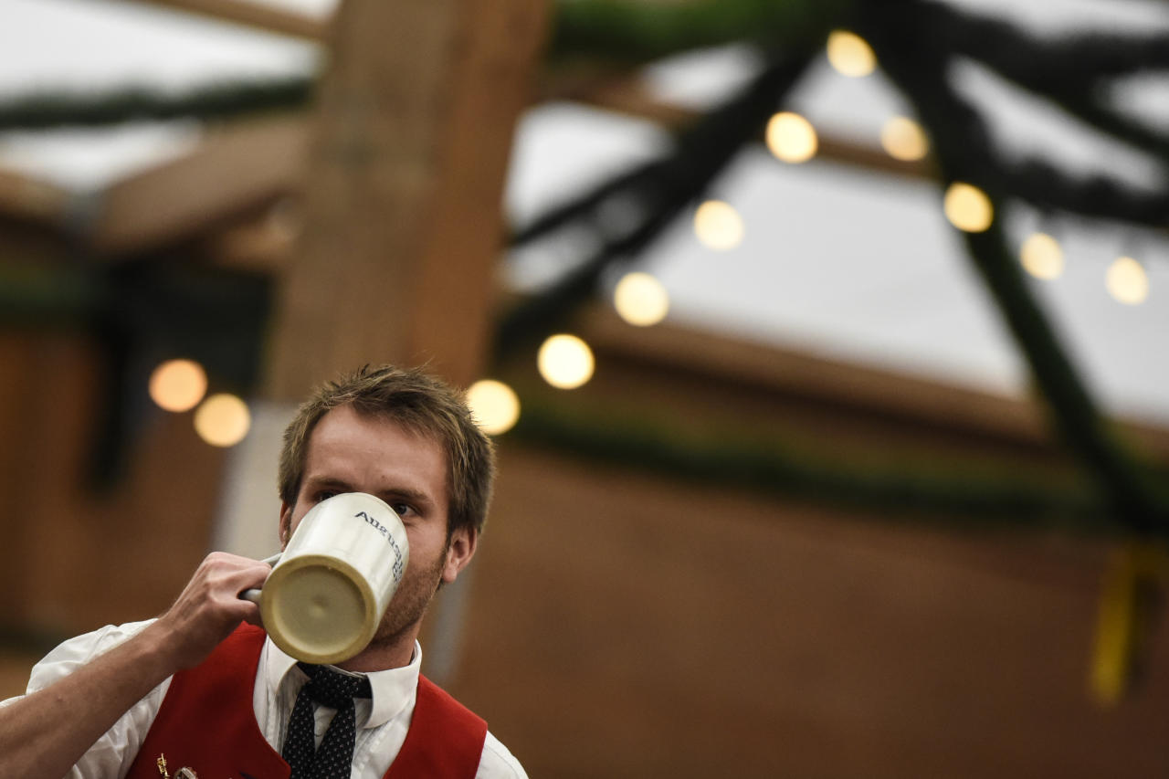 <p>A visitor drinks beer from a stone mug in the 'Tradition' tent (Getty Images) </p>