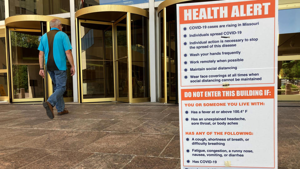 A sign warning of COVID-19 dangers remains in place Tuesday, June 15, 2021, outside the entryway of a state office building in Jefferson City, Mo. (David A. Lieb/AP Photo)