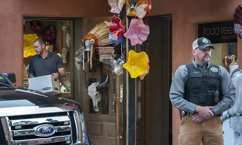 Fedral agents, left, remove evidence from the Gold House Fine Jewelry store in Santa Fe