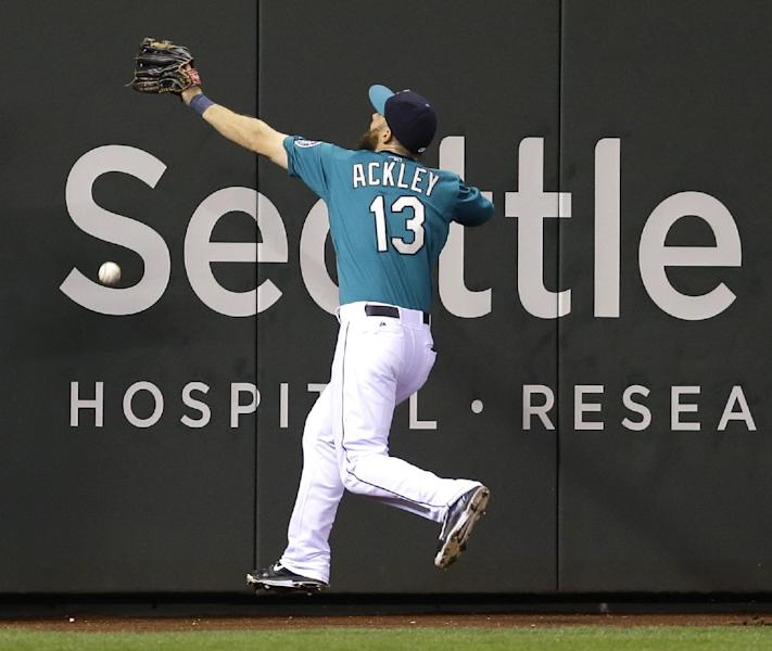 Seattle Mariners left fielder Dustin Ackley can't catch an RBI double hit by Houston Astros' Matt Dominguez Monday, April 21, 2014, in the sixth inning of a baseball game in Seattle. (AP Photo/Ted S. Warren)