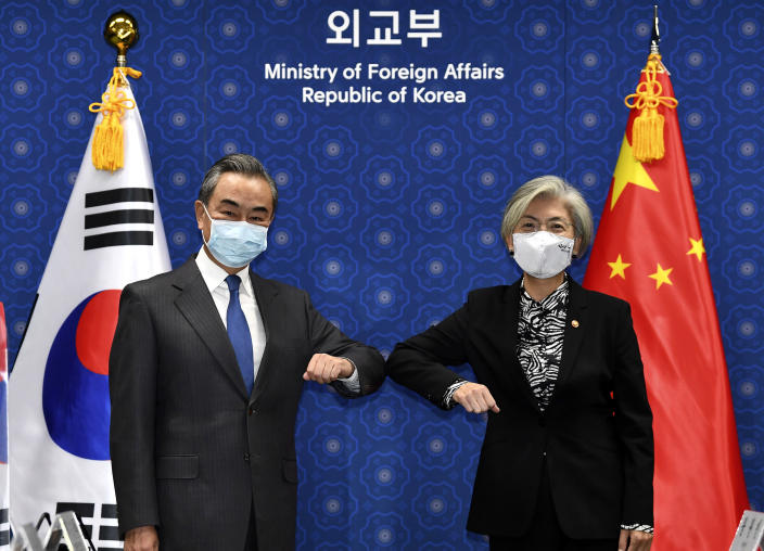 Chinese Foreign Minister Wang Yi, left, and South Korean Foreign Minister Kang Kyung-wha, right, pose together prior their meeting at the foreign ministry in Seoul, South Korea, Thursday, Nov. 26, 2020. Foreign Minister Wang arrived in Seoul on Nov. 25, for a three-day state visit to discuss bilateral high-level exchanges, the situations on the Korean Peninsula and in the region.(Kim Min-hee/Pool Photo via AP)